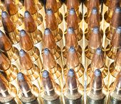 stock photo of ammo  - Ammo for a high powered rifle that has light from behind