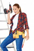 Confident happy DIY handy woman standing on a stepladder with a tool belt round her waist brandishin