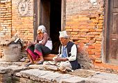 BHAKTAPUR,NEPAL-MAY 20:Old woman and man sitting intertwined their homes on May 20, 2013, Bhaktapur,