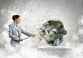 Image of businesswoman crashing globe with hammer. Ecology concept