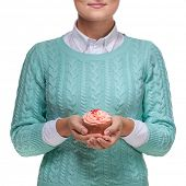Young woman holding a pink cupcake decorated with hearts, isolated on white background