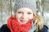 stock photo of wander  - young blond woman smiles with grey beanie and orange scarf in the winter wood - JPG