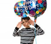 Child with a funny facial expression during his birthday party. Over white background. Balloons