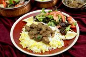 A plate of  homemade beef rogan josh, served with yellow and white rice and a salad, with typical In