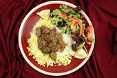 High-angle view of beef rogan josh, served with yellow and white rice and a salad. Rogan josh is usu