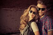 foto of denim jeans  - Couple of young people in jeans clothes posing outdoors over brick wall - JPG
