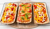 stock photo of flat-bread  - Baked flat bread with bell peppers and feta cheese and also with ham tomatoes and cheese - JPG
