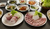 picture of kimchi  - Korean BBQ Food and side dishes spread on table.