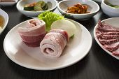 image of pork belly  - A horizontal shot of sliced pork belly with korean side dishes.