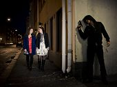 stock photo of hooligan  - Hooded man stalking two women behind a corner holding a gun - JPG
