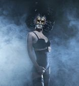 Sexy and bizarre woman in mask and lingerie over the smoky background