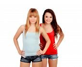 Two teen sisters with jeans shorts isolated on white background