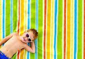 stock photo of tan lines  - happy kid sunbathing on colorful blanket blanket - JPG