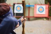 stock photo of archery  - Brunette about to shoot arrow at the archery range - JPG