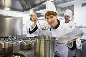 picture of saucepan  - Young female chef tasting a soup and smiling at camera in kitchen - JPG