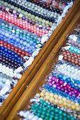 stock photo of flea  - Close view of wooden shelf with rows of colorful beaded strings with price tags on the flea market - JPG