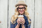 stock photo of young woman posing the camera  - Cheerful fashionable blonde holding coffee outdoors on wooden background - JPG