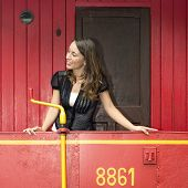 image of caboose  - Beautiful young woman standing on a red train caboose car - JPG