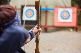 stock photo of shooting-range  - Brunette about to shoot arrow at the archery range - JPG