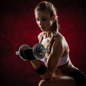 Brutal athletic woman pumping up muscles with dumbbells on red background