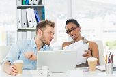 stock photo of half-dressed  - Partners working together on laptop at desk in creative office - JPG