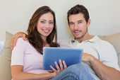 Happy relaxed young couple using digital tablet in the living room at home