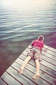 foto of dock a pond  - Boy laying on a dock looking at the water - JPG