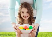 easter, family, holiday and child concept - smiling little girl and mother holding bowl with colored