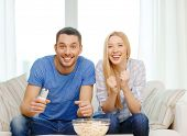 food, love, family, sports, entretainment and happiness concept - smiling couple with popcorn cheeri