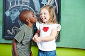 African boy kissing happy girl on the cheek in a kindergarten
