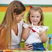 Happy girl doing paper origami with her mother in nursery