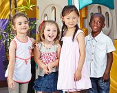 Happy interracial children together in a kids group in a kindergarten