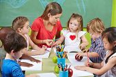 Children learning writing together in preschool with nursery teacher
