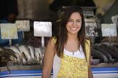 Happy beautiful woman buying fish at a fish shop street market.