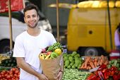 Smiling man carrying a shopping paper bag full of organic fruits and vegetables at an open street ma