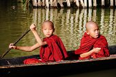Young monks rowing boat on Inle lake, Myanmar