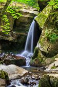 picture of incredible  - incredibly beautiful and clean little waterfall with several cascades over large stones in the forest comes out of a huge rock covered with moss - JPG