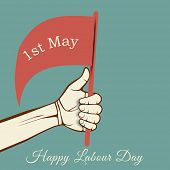 stock photo of labourer  - Human hand holding a flag with text 1st May on green background - JPG
