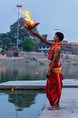 UJJAIN, INDIA - APRIL 23, 2011: Brahmin performing Aarti pooja ceremony on bank of holy river Kshipr