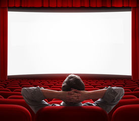 image of cinema auditorium  - one relaxed man sitting alone with comfort like at home in front of big screen in empty cinema hall - JPG