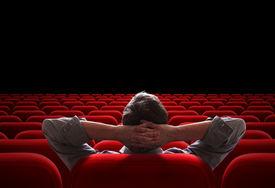 stock photo of cinema auditorium  - one man sitting in empty cinema or theater auditorium - JPG