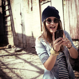 pic of long distance  - Pretty young woman using mobile phone and getting photos - JPG