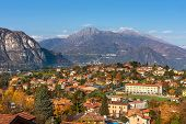View of small town surrounded by mountains on the shores of Lake Como in autumn in Italy.