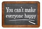 you can not make everyone happy - motivational phrase  on a vintage slate blackboard