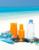 Bottle Of Water And Sun Protection Cream On Beach Background