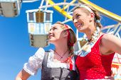 Friends visiting together Bavarian fair in national costume or Dirndl in front of ferris wheel