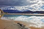 After the storm. Gray lake in the national park Torres del Paine in Chilean Patagonia. Clouds are reflected in ice water of the lake. The blue iceberg is in the distance visible