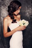 Beautiful Bride With Dark Hair In Elegant Wedding Dress With Bouquet Of Flowers