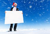 Christmas businessman holding blank placard on top of a mountain.