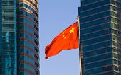 The Chinese flag with a modern building background.